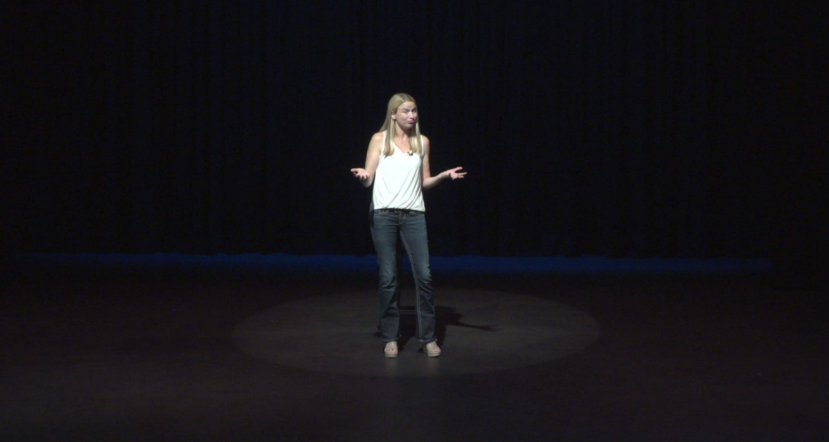 Woman standing on dark stage in spotlight shrugging